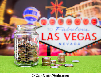 Coins in glass bottle with Las vegas sign on background