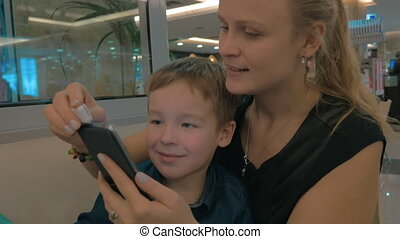 Mother and child using magnetic mobile card reader - Mother...