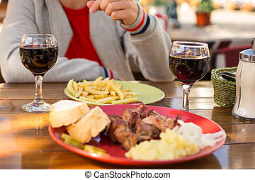 lunch at the cafe, kebab with fries and glasses of wine