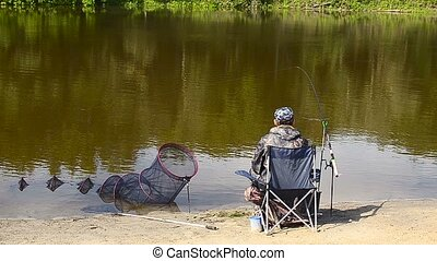 fisher man is fishing on the bank of the river, the lake on...