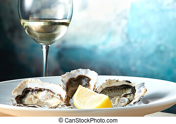 Oysters in a white plate with lemon