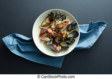 Plate of mussels in garlic sauce on a napkin blue and black...