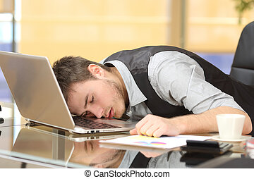 Tired businessman sleeping over a laptop at job - Tired...