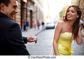 Lady in yellow sticks out her tongue at man in black suit