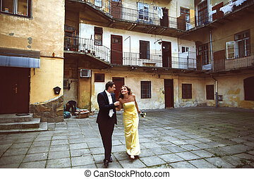 Couple walks inside the court of house with balcony
