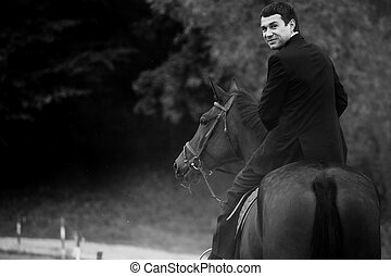 Man in black suit turns while he rides a horse