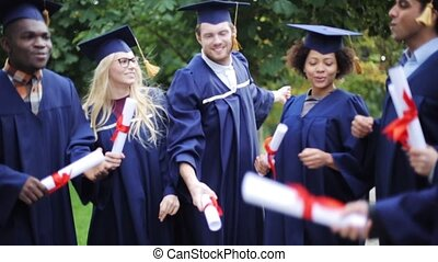 happy students in mortar boards with diplomas - education,...