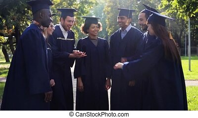 happy students in mortar boards with hands on top -...