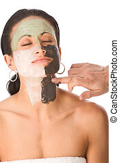 Spa treatment - color facial mask on ethnic woman - Hand of...