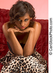 Portrait of glamorous ethnic female sitting on couch