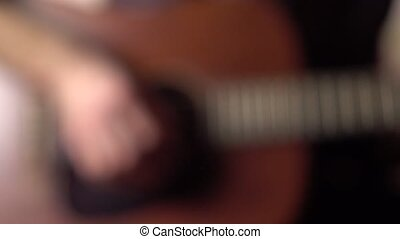 Defocused guitar player's hand touching strings. Music...