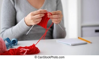 woman knitting with needles and red yarn - people and...