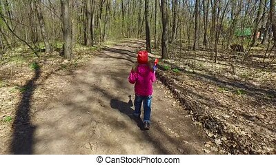 The child did not like the road. She decided to align the road. Girl having fun, running in the woods. Sunny spring day. Beautiful weather.