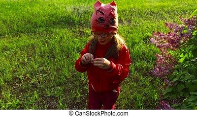 Child girl exploring flower lilac bush. Beautiful sunny...