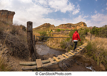 Woman hiker crossing hanging footbridge, suspended on stream, in the majestic Golden Gate Highlands National Park, South Africa. Concept of adventure and traveling people. Fish eye view.
