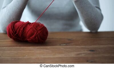 woman knitting with crochet hook and red yarn - people and...