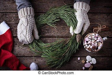 Woman in mittens making Christmas wreath. Selective focus,...