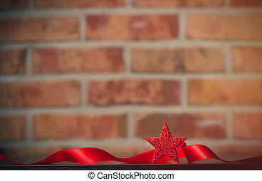 Ribbon and little red star on a table on brick wall...