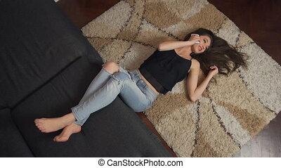 Attractive Girl Phone Talking Lying on Floor Carpet