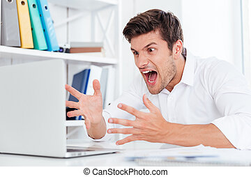 Furious angry young businessman working with computer and...