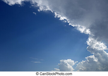 Blue sky with rain clouds and sun