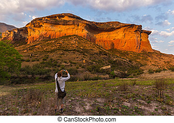 Tourist holding smart phone and taking photo at scenic cliff illuminated by sunset light in the majestic Golden Gate Highlands National Park, famous travel destination in South Africa.