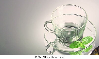 Tea being poured into glass tea cup. HD