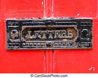 Letterbox - An antique iron letterbox framed by a bright red...