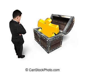 Businessman looking at golden jigsaw puzzle piece in treasure chest