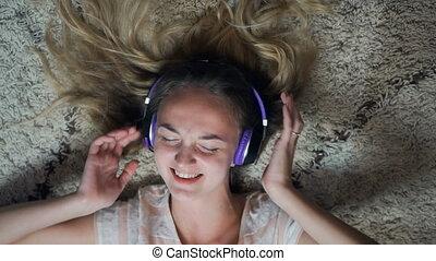 Beautiful Blonde Girl Listening Music Lying on Carpet