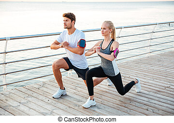 Athletic young couple sitting and stretching legs together...