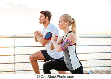Side view of a sport couple warming up before jogging - Side...