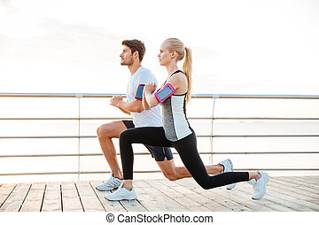 Sporty couple warming up before jogging at the beach - Side...