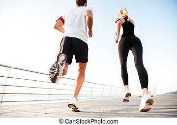Back view of a young couple jogging at beach pier in the...