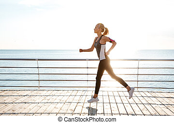Beautiful young sportswoman training and running on pier in...