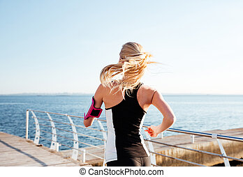 Back view of young woman exercising on the sea pier - Back...