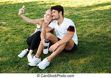 Sport man and woman making selfie in park after jogging -...