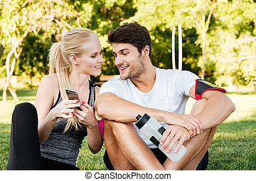 Smiling young woman and personal trainer with smartphone...