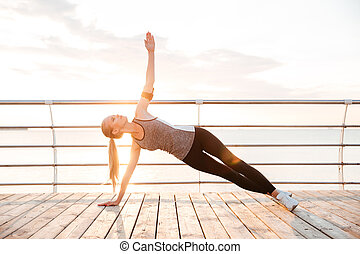 Sporty fitness woman doing planking yoga exercises outdoors...