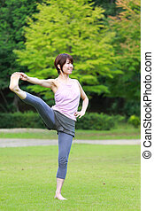 Japanese woman outside doing yoga Extended Hand-To-Big-Toe...