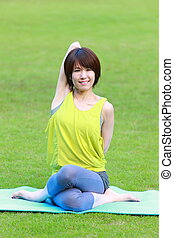 Japanese woman outside doing yoga cow face pose - Portrait...