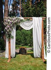 arch for the wedding ceremony of beige cloth and wooden logs...