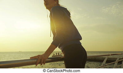 Active young lady running on wooden boardwalk near the sea.