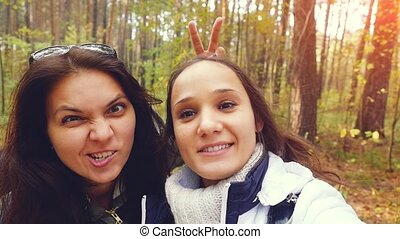 Two beautiful girls with cell phone camera taking photos in...