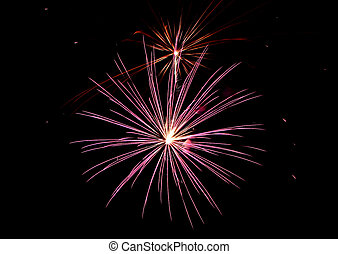 Pink, white and orange fireworks light the sky on the 4th of...