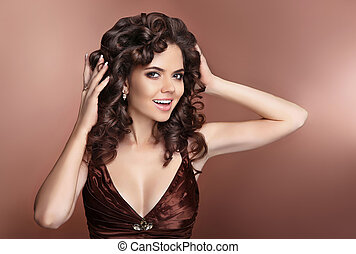 Attractive laughing brunette girl with healthy curly hairstyle and makeup, manicured nails.
