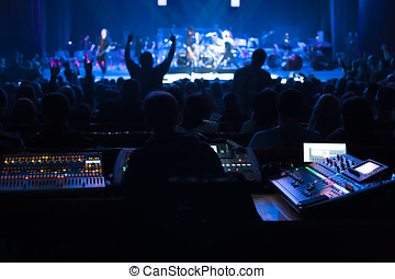 Soundman working on the mixing console. - Soundman working...