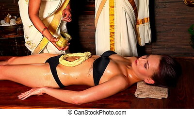Woman having Indian stomach exotic treatment spa using...