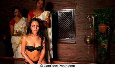 White woman having professional head treatment. Indian masseuse in spa salon.
