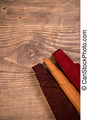 Brown,orange and red leather in rolls, on wooden background....